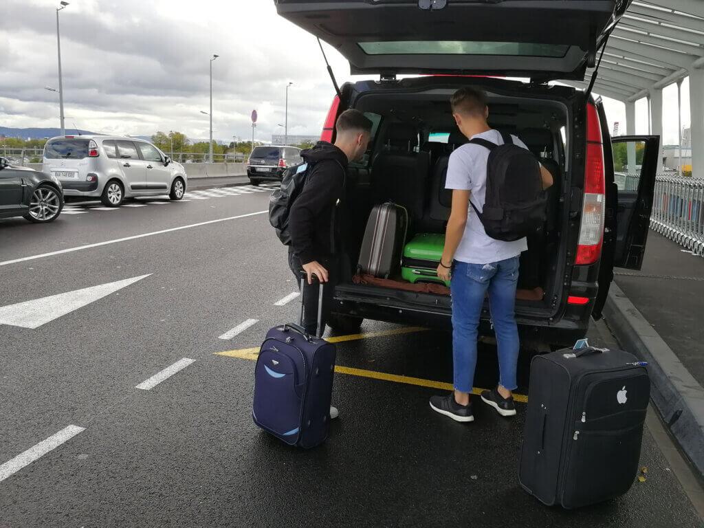 Deux invités se tiennent à côté du taxi et prennent les bagages.